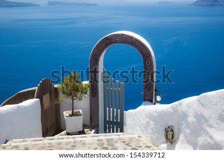 gate decorated by pot of plant beside the Aegean sea, Santorini, Greece  - stock photo