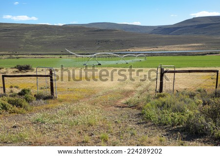 Gate leading to an agricultural farm with an irrigation system in the Northern Cape of South Africa - stock photo