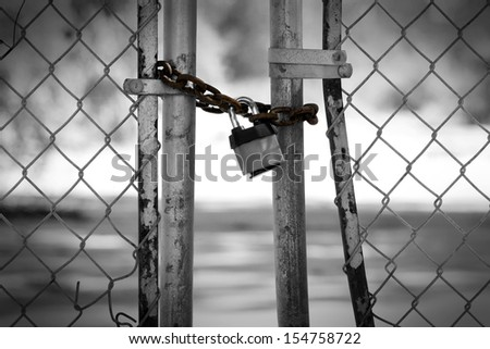Gate locked with padlock at abandoned factory - stock photo