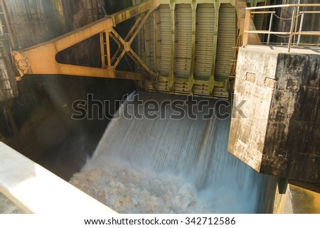 Gate of hydroelectric power plant letting excess of water overflow - stock photo