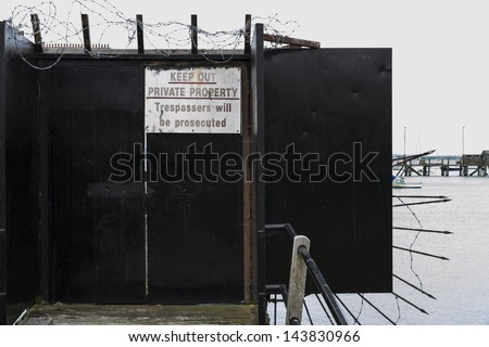 Gate preventing access to jetty with warning sign -Private property keep out trespassers will be prosecuted - stock photo