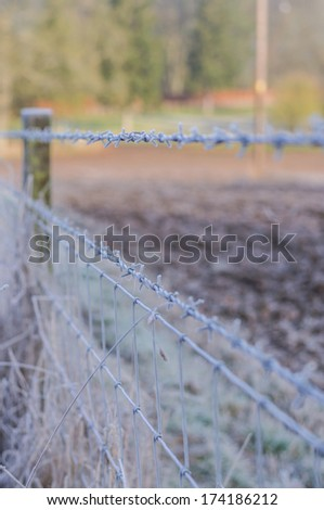 Gate with barbed wire and wooden post fences on countryside - stock photo