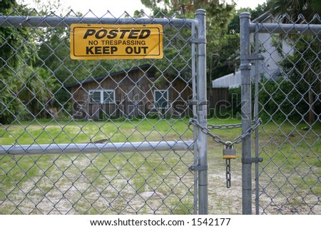 Gate with Keep Out Sign and house in background - stock photo
