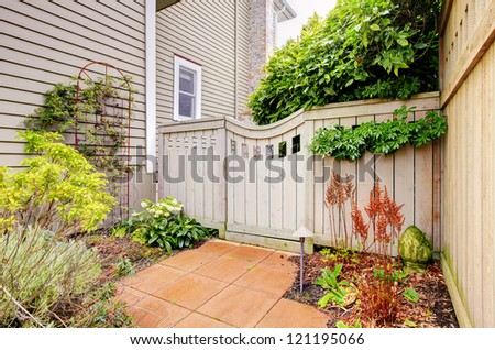 Gates and fence to the backyard with side of the house. - stock photo