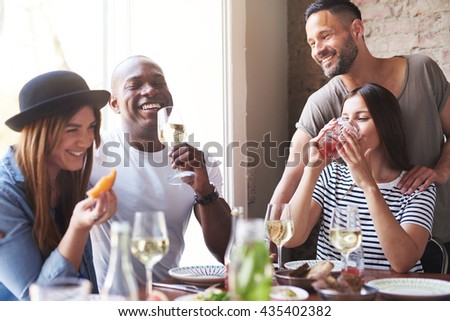 Gathering of four diverse laughing adults enjoying wine and appetizers at lunch with each other at restaurant table beside large bright window - stock photo