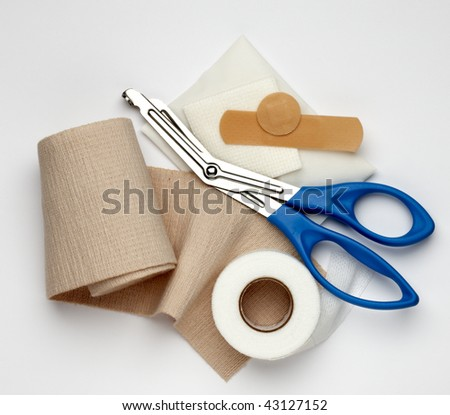 Gauze, ace bandage, tape, scissors and bandages shot on white background with a soft shadow - stock photo
