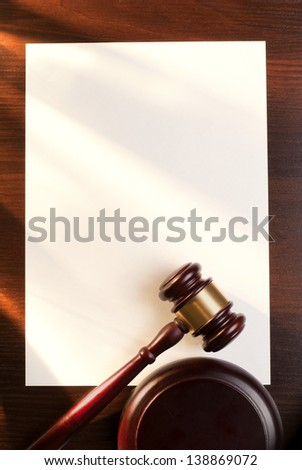 gavel and a sheet of paper on the brown table - stock photo