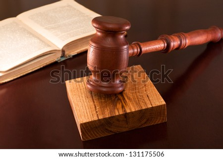 Gavel and book of justice on the table in the courtroom - stock photo