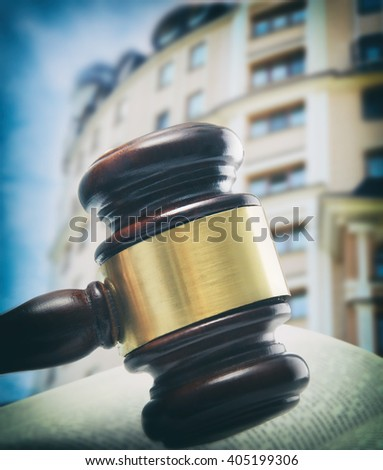 Gavel and book on wooden table on building background. Auction concept - stock photo