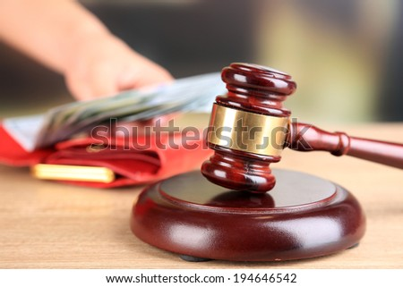 Gavel and hand holding money in wallet on wooden background