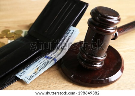 Gavel and money coins on wooden background - stock photo