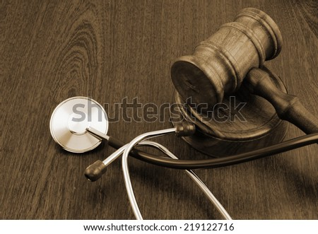 Gavel and stethoscope on table with room for text  - stock photo