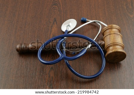 Gavel and stethoscope on wooden table - stock photo