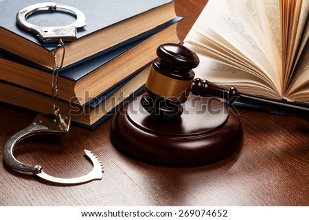 Gavel, books and handcuffs on wooden table - stock photo