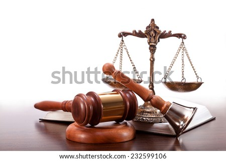 Gavel, bronze scales, a book and a bell on the table - stock photo
