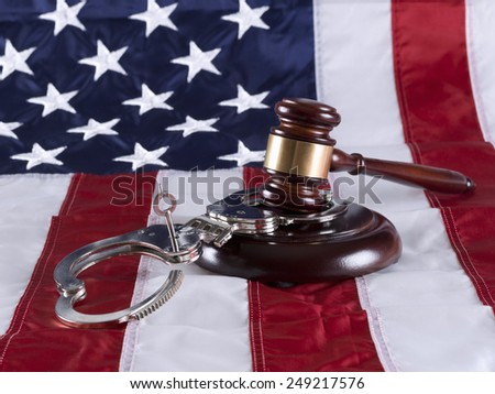 Gavel, handcuff and American flag - stock photo