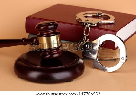 Gavel, handcuffs and book on law on beige background - stock photo