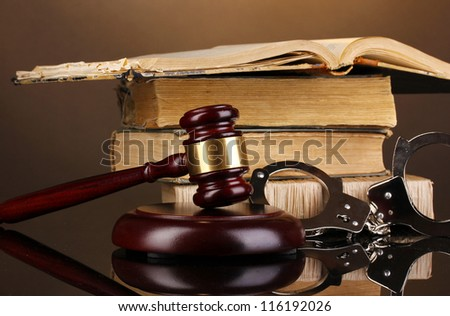 Gavel, handcuffs and book on law on brown background