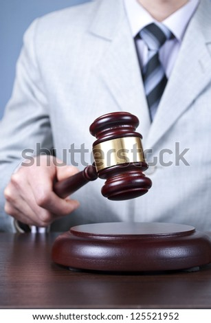 gavel in the hand of a man in a business suit - stock photo