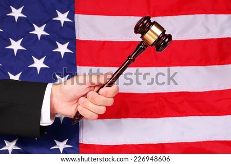 Gavel on Judge Hand over American Flag - stock photo