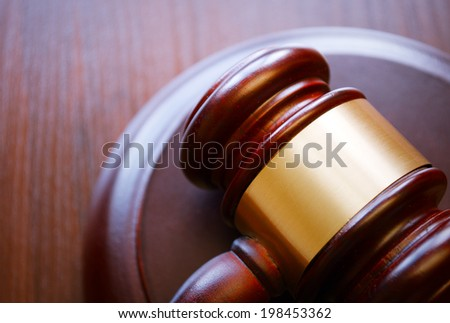 Gavel on sounding block on wooden surface - stock photo