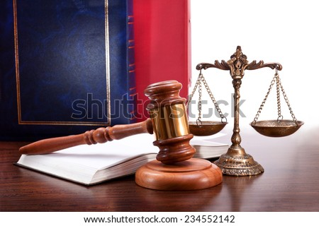 Gavel, scales, open book and court cases on the table - stock photo