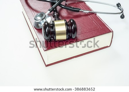 Gavel, stethoscope and book on white background - stock photo