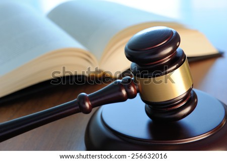 Gavel with book on wood surface