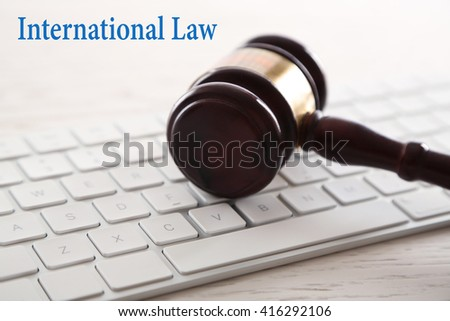 Gavel with computer keyboard on wooden table closeup. International law concept - stock photo