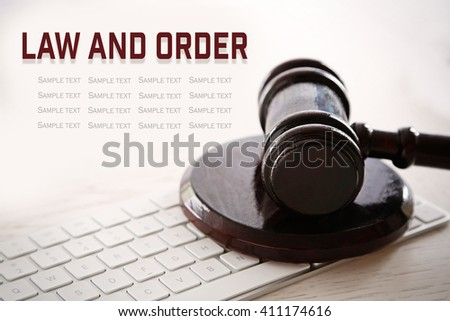 Gavel with computer keyboard on wooden table closeup. Law and order concept - stock photo