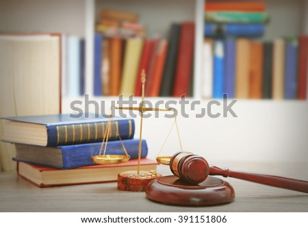 Gavel with justice scales and stack of books on wooden table - stock photo