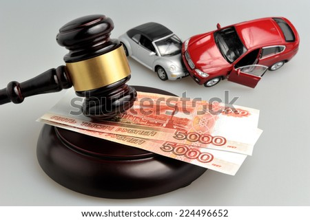 gavel with money and toy cars accident on gray background - stock photo