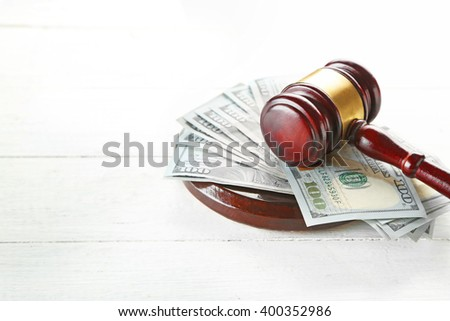 Gavel with money on wooden background - stock photo