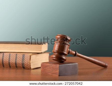 Gavel. Wooden mallet and books on a green background - stock photo