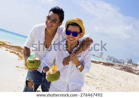 Gay couple drinking a coconut in the Caribbean - stock photo