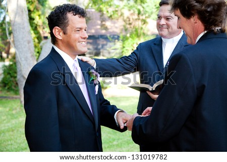 Gay couple exchanges rings during their wedding ceremony.