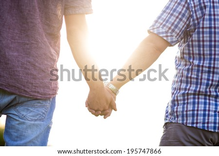 Gay couple holding hands and enjoying the summer - stock photo