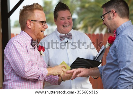 Gay couple in wedding ring ceremony with minister - stock photo