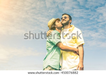 Gay couple kissing outdoor on a sky background. Concept about homosexual, love and lifestyle - stock photo