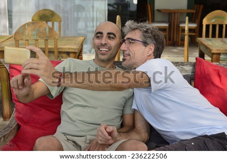 Gay couple taking a selfie with mobile phone in a cafe - stock photo