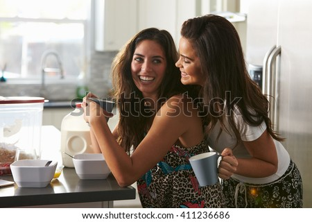 Gay female couple in their 20s embracing in  in the kitchen - stock photo