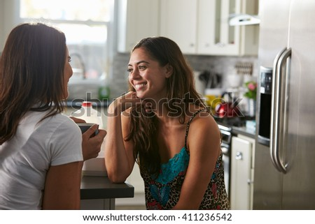 Gay female couple in their 20s talking in their kitchen - stock photo