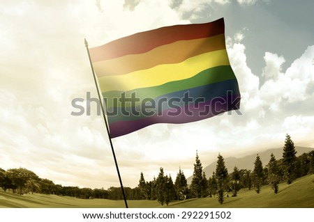 Gay flag on the pole in the hill over blue sky - stock photo