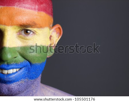 Gay flag painted on the face of a man. Man is looking at camera and is smiling - stock photo