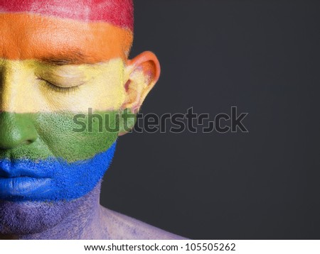 Gay flag painted on the face of a man.The man's eyes are closed with a serene expression on his face - stock photo