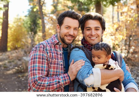 Gay Male Couple With Baby Walking Through Fall Woodland - stock photo
