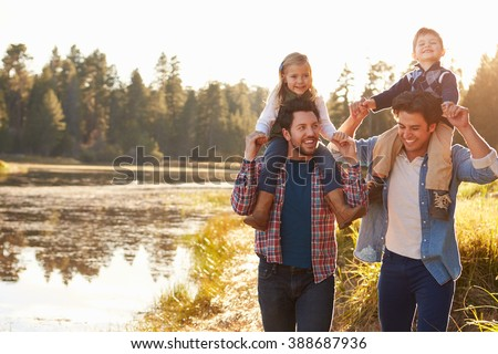 Gay Male Couple With Children Walking By Lake - stock photo