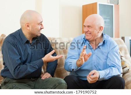 Gay men talking on  couch at home - stock photo