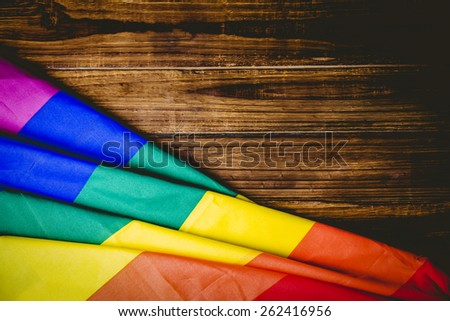 Gay pride flag on wooden table shot in studio - stock photo