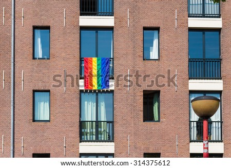 gay rainbow flag hanging out of a window during the 2015 gay pride amsterdam